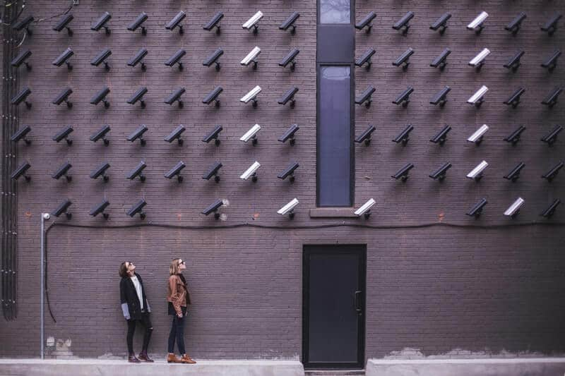 Two people looking at white and black security cameras